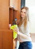 Szczęśliwa blondynki dziewczyna wyciera pył Obrazy Stock