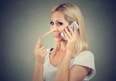 Szczęśliwa blondynki kobieta opowiada na telefonie komórkowym mówi kłamstwa z długim nosem Kłamcy pojęcie obraz royalty free