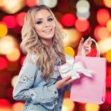 Szczęśliwa blondynki kobieta uśmiecha się torbę na zakupy i trzyma obrazy stock
