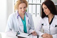 Szczęśliwa blondynki kobiety lekarka i pacjent dyskutuje badanie medyczne rezultaty Medycyny, opieki zdrowotnej i pomocy pojęcie, obrazy royalty free