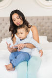 Szczęśliwa brunetka trzyma jej dziecka i używa smartphone Zdjęcie Stock
