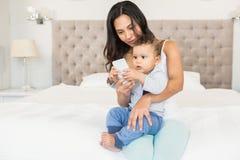 Szczęśliwa brunetka trzyma jej dziecka i używa smartphone Zdjęcie Royalty Free