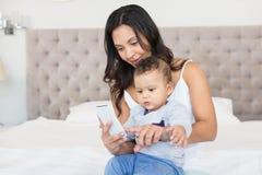 Szczęśliwa brunetka trzyma jej dziecka i używa smartphone Obrazy Royalty Free