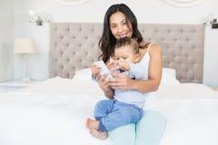 Szczęśliwa brunetka trzyma jej dziecka i używa smartphone Obraz Stock