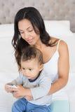 Szczęśliwa brunetka trzyma jej dziecka i używa smartphone Fotografia Royalty Free