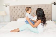 Szczęśliwa brunetka trzyma jej dziecka który trzyma smartphone Obrazy Stock