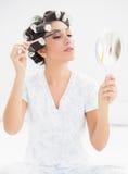Szczęśliwa brunetka w włosianych rolownikach patrzeje w ręki lustrze i brushi obrazy stock