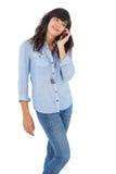 Szczęśliwa brunetka z jej telefonem komórkowym dzwoni someone Zdjęcie Royalty Free