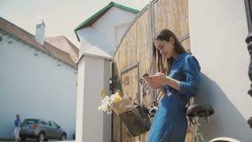 Szczęśliwa brunetki dziewczyna śmia się i opowiada na telefonie z rowerem i kwiatami w koszykowym, używać jej smartphone, wolny m zbiory