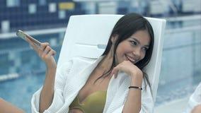 Szczęśliwa brunetki kobieta opowiada na telefonie na deckchair z jej uśmiechniętym żeńskim przyjaciela obsiadaniem obok ona zbiory