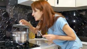 Szczęśliwa brunetki kobieta stoi bezczynnie kuchenkę w kuchni i wącha ładnych aromaty od jej posiłku w niecce, kucharstwo zbiory wideo