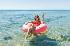 Szczęśliwa brunetki kobieta w różowym nadmuchiwanym pączku w lato słonecznym dniu zdjęcie royalty free