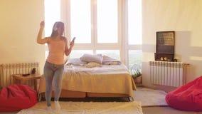 Szczęśliwa brunetki młoda kobieta tanczy samotnie w sypialni z dużym okno w hełmofonach słucha muzyka na smartphone, dziewczyna zdjęcie wideo