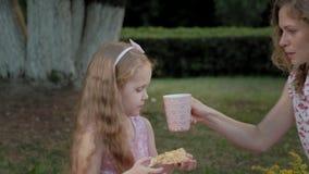 Szczęśliwa córka i matka pijemy herbaty na przesłonie Rodzina w miasto parku na pinkinie na ciepłym wieczór przy zmierzchem zbiory wideo