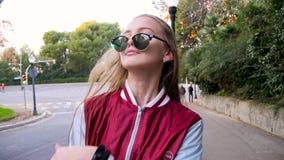Szczęśliwa caucasian nastoletnia dziewczyna z blondynu i szkieł pozami dla portreta Okularów przeciwsłonecznych spada puszek na t zbiory wideo