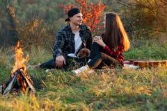 Szczęśliwa caucasian para z ich śmiesznym psim obsiadaniem na gazonie w wiosna parku Młody człowiek i jego dziewczyna cieszy się  zdjęcia stock