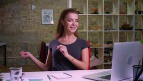Szczęśliwa caucasian pracująca miedzianowłosa kobieta jest przyglądająca jej laptopu ekran i ono uśmiecha się podczas gdy klasczą