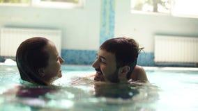 Szczęśliwa caucasian rodzina trzy jest wisząca w pływackim basenie out wpólnie Szczęśliwa żona całuje jej męża ich zbiory wideo