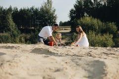 Szczęśliwa caucasian rodzina w biel sukni, matce i tacie bawić się z małą dziewczynką z piaskiem, bawi się bawić się w piaskownic zdjęcie stock