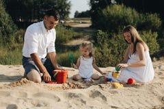 Szczęśliwa caucasian rodzina w biel sukni, matce i tacie bawić się z małą dziewczynką z piaskiem, bawi się bawić się w piaskownic obraz stock
