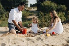 Szczęśliwa caucasian rodzina w biel sukni, matce i tacie bawić się z małą dziewczynką z piaskiem, bawi się bawić się w piaskownic fotografia stock