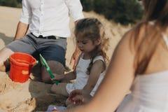 Szczęśliwa caucasian rodzina w biel sukni, matce i tacie bawić się z małą dziewczynką z piaskiem, bawi się bawić się w piaskownic obrazy stock