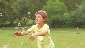 Szczęśliwa chłopiec bawić się chwytów mydlanych bąble na ogródzie swobodny ruch z bliska zbiory wideo