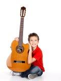 Szczęśliwa chłopiec bawić się na gitarze akustycznej Zdjęcie Royalty Free