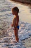 Szczęśliwa chłopiec bawić się w fala na plaży Rozochocona chłopiec kąpać w dennych fala przy zmierzchem obrazy stock