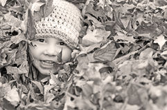 Szczęśliwa chłopiec bawić się w liściach Zdjęcia Royalty Free