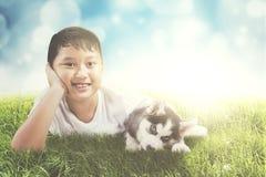 Szczęśliwa chłopiec bawić się z łuskowatym szczeniakiem Obraz Stock