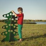 Szczęśliwa chłopiec bawić się z papierowym drzewem Zdjęcia Royalty Free