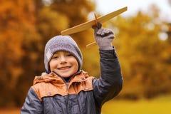 Szczęśliwa chłopiec bawić się z zabawka samolotem outdoors Zdjęcie Stock