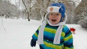 Szczęśliwa chłopiec biega w parku w zimie Szczęśliwa chłopiec ma zabawę w śnieżnym zima parku uśmiecha się miękkie ogniska, zdjęcie wideo