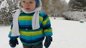 Szczęśliwa chłopiec biega w parku w zimie Szczęśliwa chłopiec ma zabawę w śnieżnym zima parku uśmiecha się miękkie ogniska, zbiory