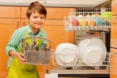 Szczęśliwa chłopiec ciągnie out cutlery zmywarka do naczyń zdjęcia stock
