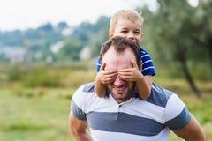 Szczęśliwa chłopiec cieszy się z jazdą na ojca ` s plecy Fotografia Stock