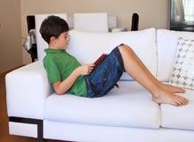 Szczęśliwa chłopiec Czyta książkę Obrazy Royalty Free