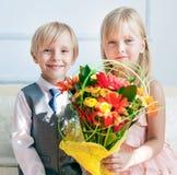 Szczęśliwa chłopiec daje bukietowi dla ślicznej dziewczyny fotografia stock
