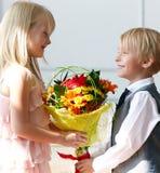 Szczęśliwa chłopiec daje bukietowi dla ślicznej dziewczyny obraz royalty free