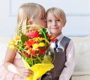 Szczęśliwa chłopiec daje bukietowi dla ślicznej dziewczyny fotografia royalty free