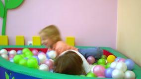 Szczęśliwa chłopiec i dziewczyna bawić się w wielo- coloured balowym basenie Przedszkole zbiory
