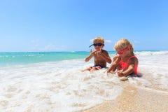 Szczęśliwa chłopiec i dziewczyna bawić się z wodą na plaży Fotografia Royalty Free