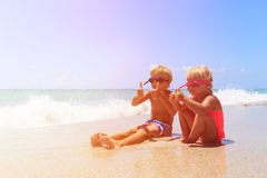 Szczęśliwa chłopiec i dziewczyna bawić się z wodą na plaży Zdjęcia Royalty Free