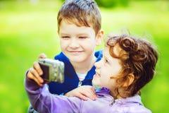 Szczęśliwa chłopiec i dziewczyna bierze jaźni fotografię w jesień parku Obraz Royalty Free