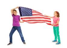 Szczęśliwa chłopiec i dziewczyna lata flaga amerykańską Obraz Stock