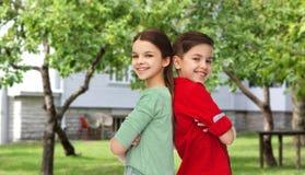 Szczęśliwa chłopiec i dziewczyna stoi wpólnie nad podwórkem Obrazy Stock