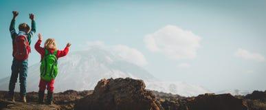 Szczęśliwa chłopiec i dziewczyna wycieczkuje w górach fotografia stock