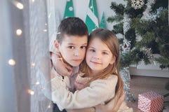 Szczęśliwa chłopiec i dziewczyna z jego Bożenarodzeniowym prezentem Boże Narodzenia, wakacje i prezenty, zdjęcie royalty free