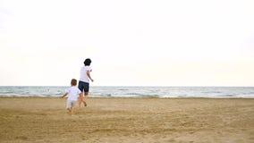 Szczęśliwa chłopiec i jego mama biegamy wzdłuż plaży za each inny, przeciw tłu morze zdjęcie wideo